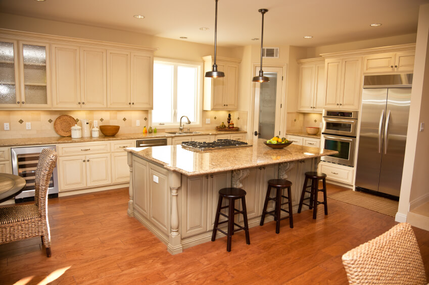Warm Toned Hardwood Flooring And Massive Marble Topped Island Anchor This Kitchen Featuring White Cabinetry