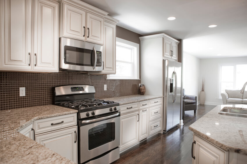Contrasting tones of dark brown and white throughout this kitchen, with  natural hardwood flooring and