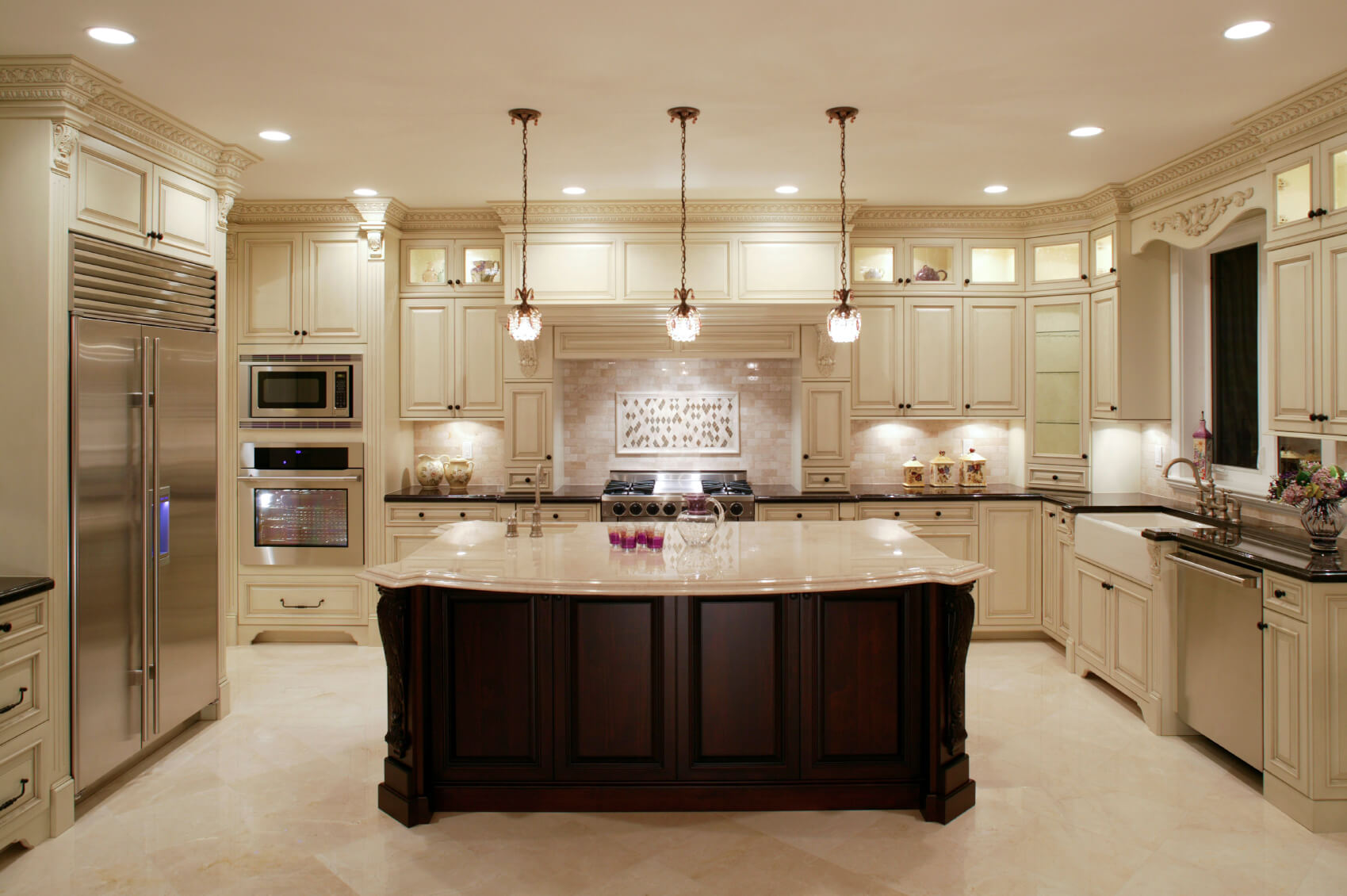 This U-shaped kitchen centers around a large dark wood island with classic  marble countertop