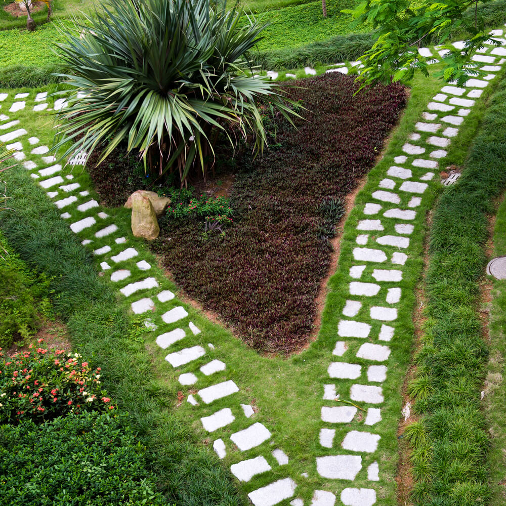 this sparse spaced out flagstone walkway splits around a triangular garden - Flagstone Walkway Design Ideas