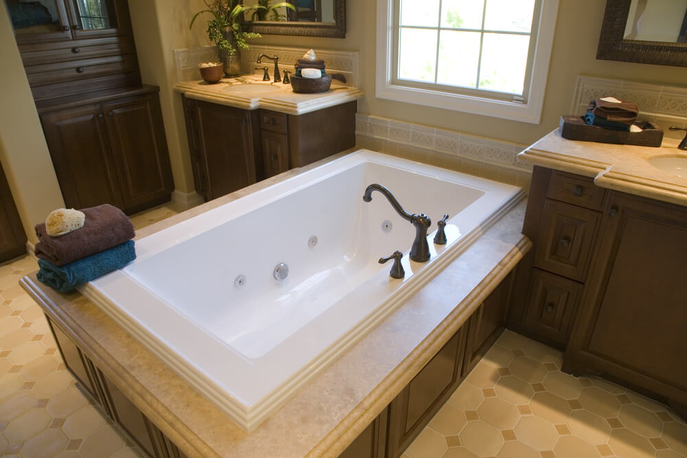 soaking tub enclosure in dark wood with beige marble top sits beneath window and between matching