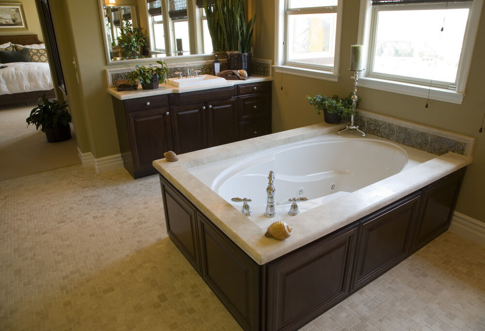 in a bathroom featuring patterned beige tile flooring and dark wood cabinetry this oval soaking