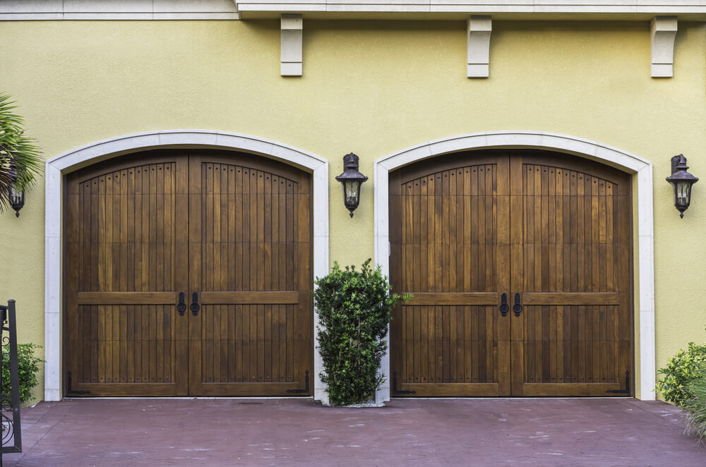 Garage Doors Designs garage design pics collection carriage garage door designs Garage Featuring Twin Arched Carriage Style Doors In Dark Stained Natural Wood Flanked By Ornate