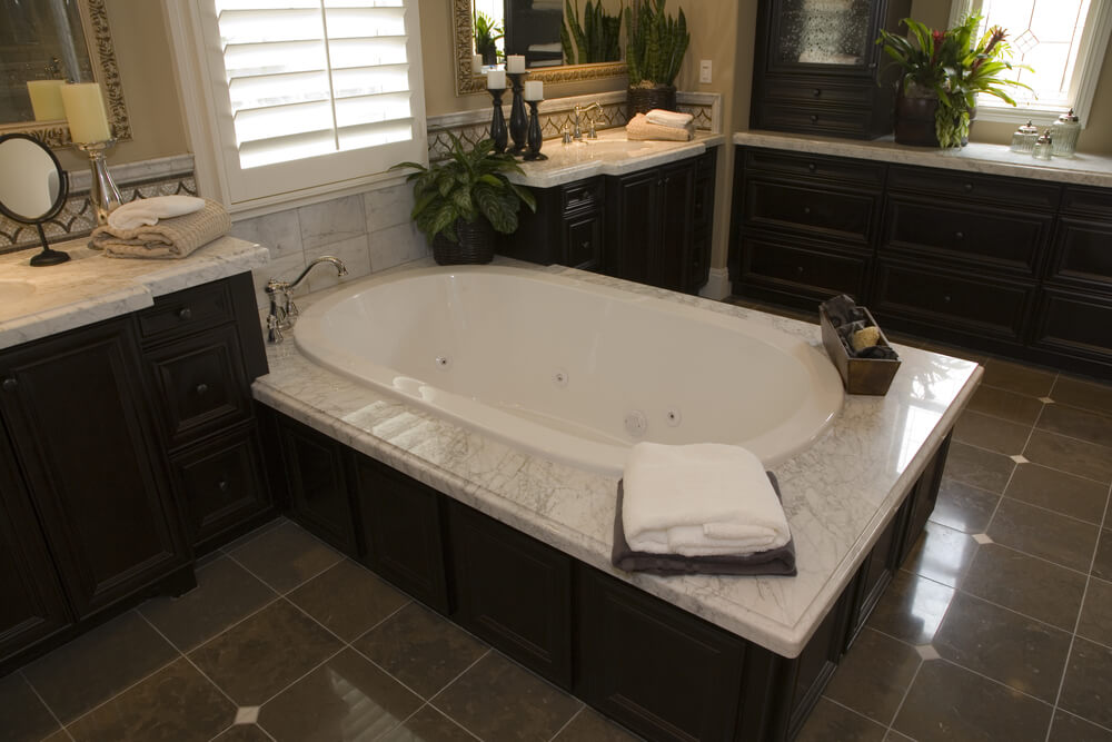 large soaking tub rests on marble topped dark wood enclosure between matching vanity counters