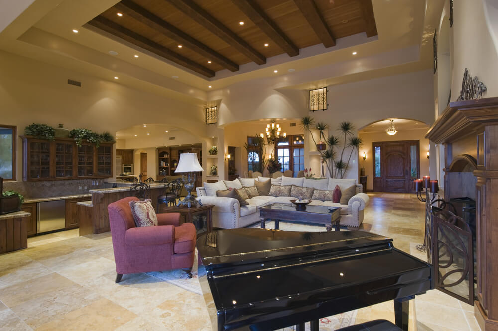 Expansive open space holds this pillow backed living room sectional sofa at its center, surrounded by rich dark wood furniture over beige marble flooring. High ceiling with exposed beams sits above space shared with kitchen area.