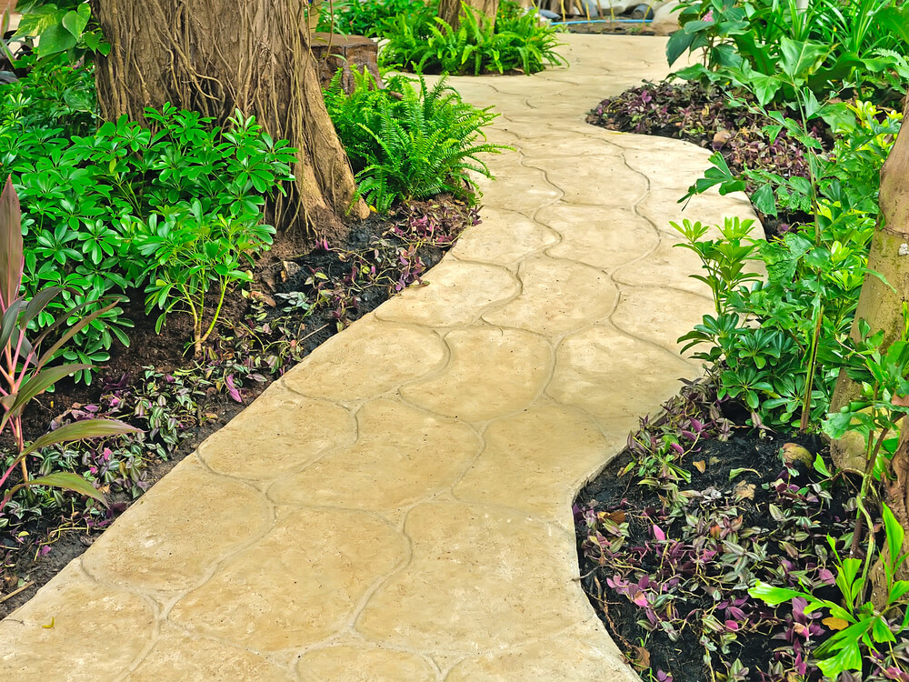 beige toned walkway in curved natural pattern weaves through this tropical garden