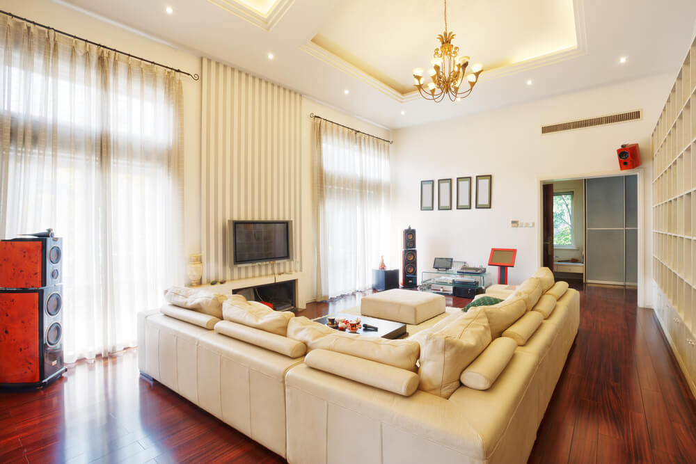 cherry wood flooring supports large beige leather living room sectional sofa in this high ceiling space