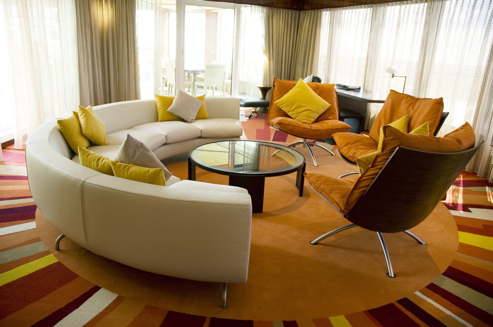 Circular Living Room Features Bright Multi Colored Sun Pattern Carpeting With Semi