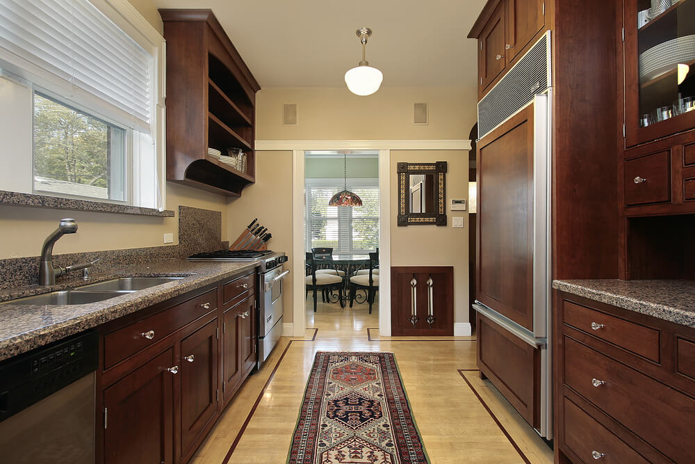 heres a classic galley or corridor kitchen layout with dark wood cabinets - Galley Kitchen Design Ideas