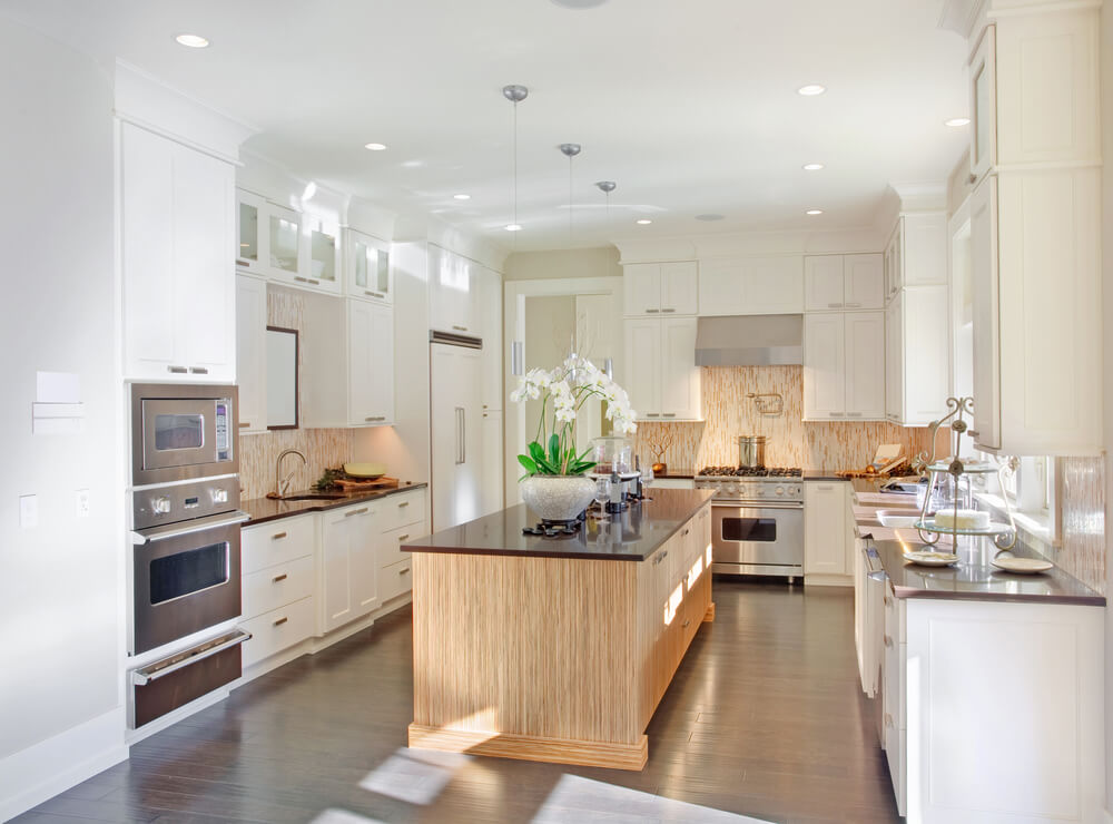 this kitchen sandwiches light natural wood texture between layers of white cabinetry with large matching - Large Kitchen Layouts