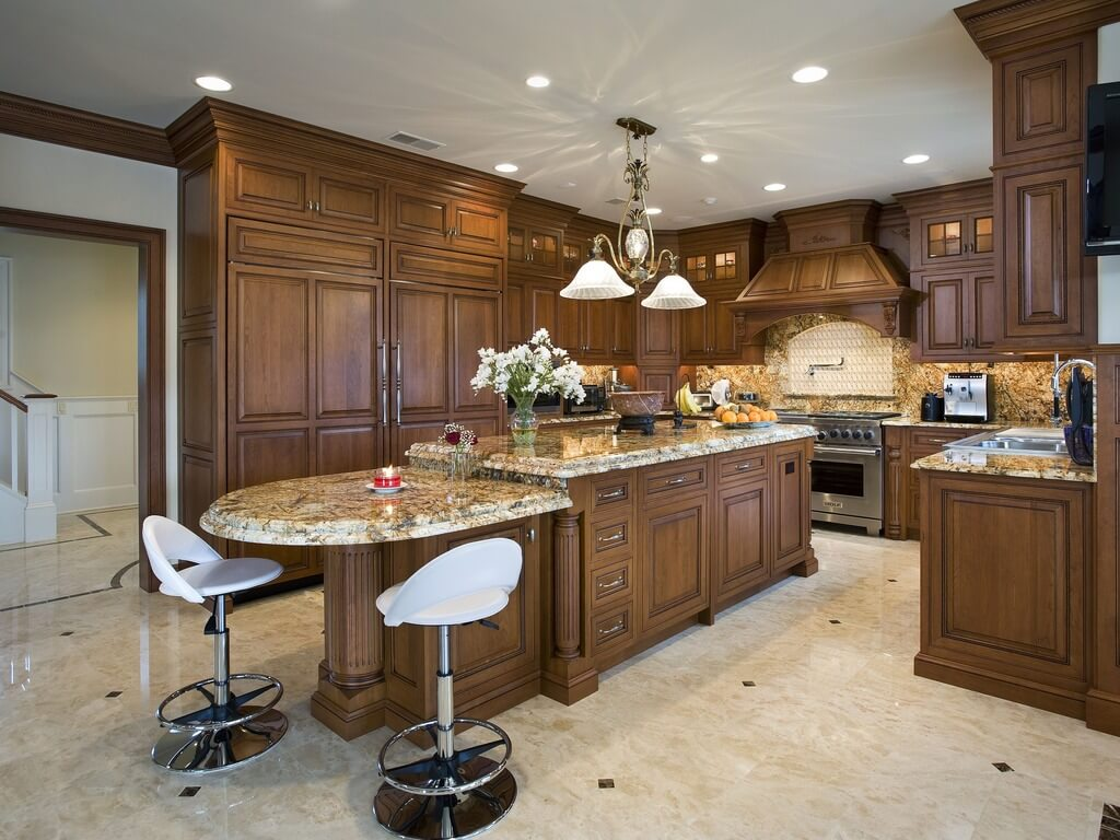 Traditional wood island matching cabinetry throughout this kitchen features marble countertop and circular dining area extension.