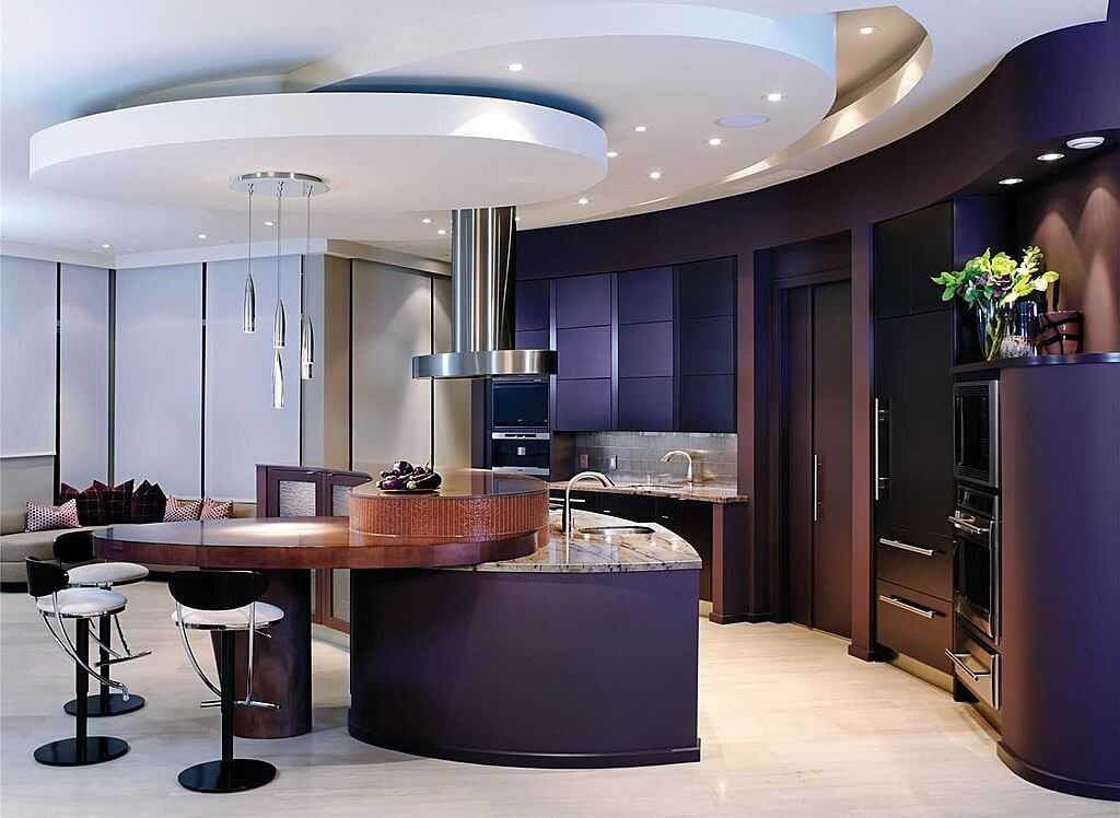 Luxurious, modern kitchen awash in dark purple and wood tones featuring marble topped island with extended dining table attached.