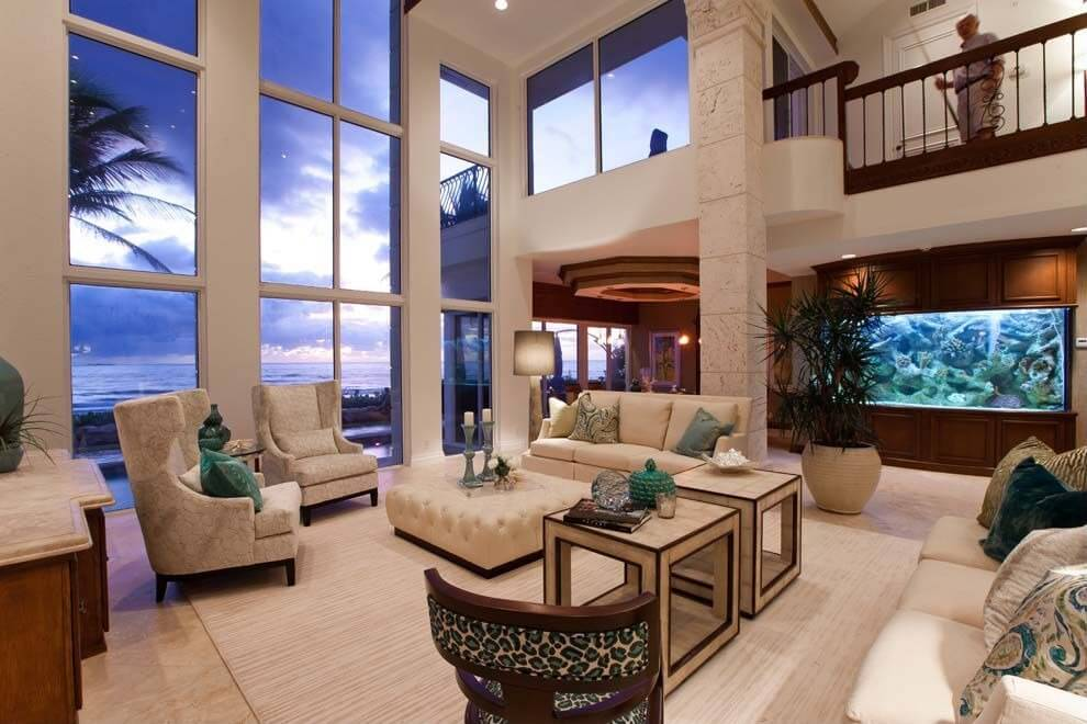 Two story living room featuring floor to ceiling views of the ocean features beige toned furniture set centered around large button tufted square ottoman with removable tray table on cushion surface.