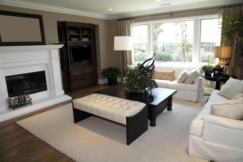 Black wood frame with white tufted leather bench ottoman, seated next to large black wood coffee table, center this white and tan living room with matching couches and natural hardwood flooring.