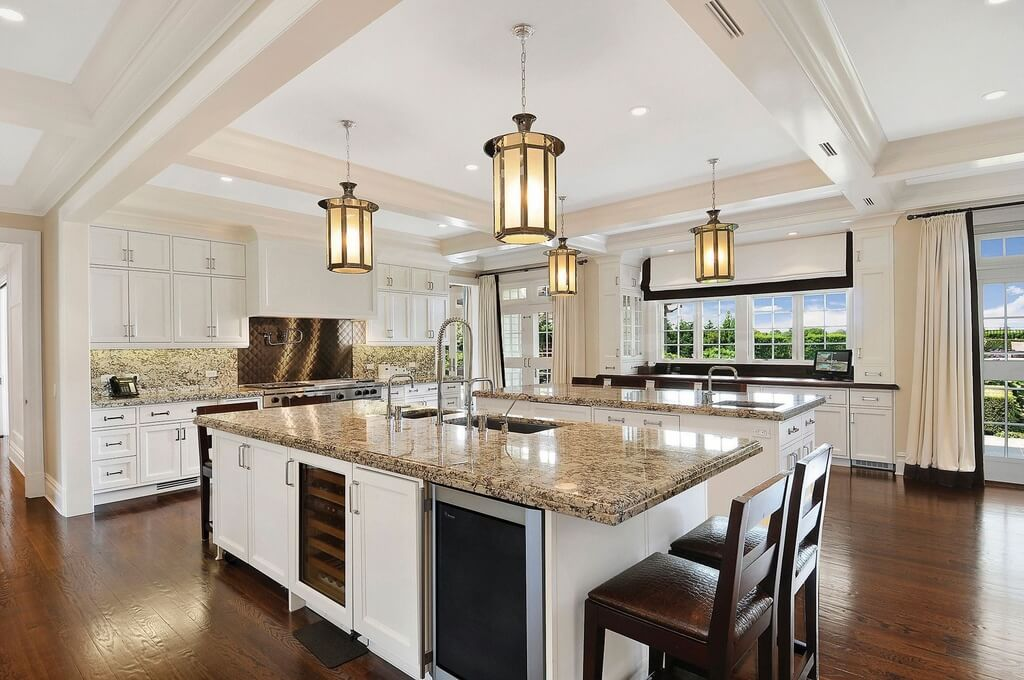huge white kitchen with dark wood flooring the wall of windows