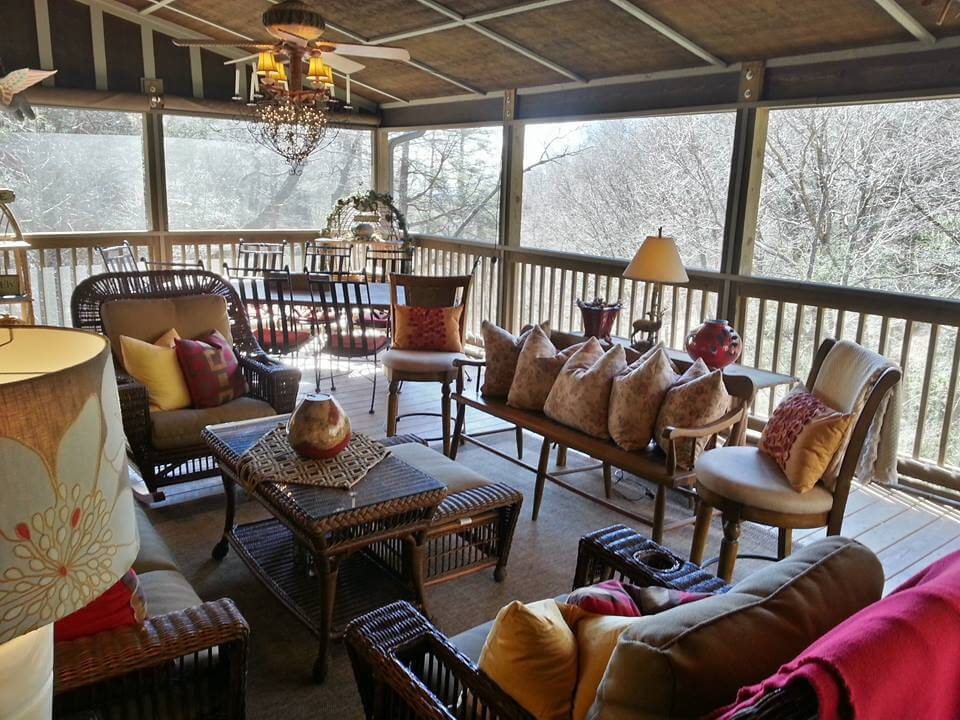 This traditionally styled upper level patio features an array of wicker furniture with grey cushions, full dining table in corner, and arched roof with exposed beams, over hardwood flooring.