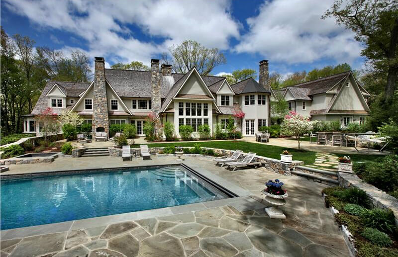 This sprawling mansion features expansive stone patio, extending to multiple areas, including exterior stone fireplace and large swimming pool area.
