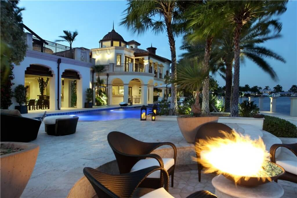 Sprawling, Spanish style mansion features extensive stone patio, with large swimming pool and lowered fire pit area with black and white wicker chairs surrounding.