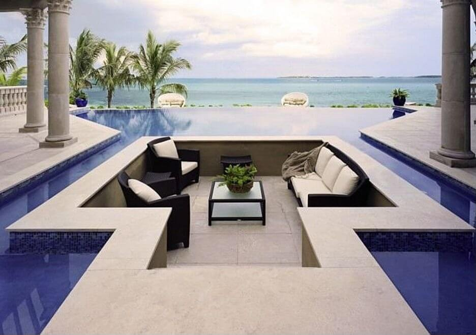 "This striking patio features a ""floating"" conversation pit set into blue framed infinity pool, between stone pillars."