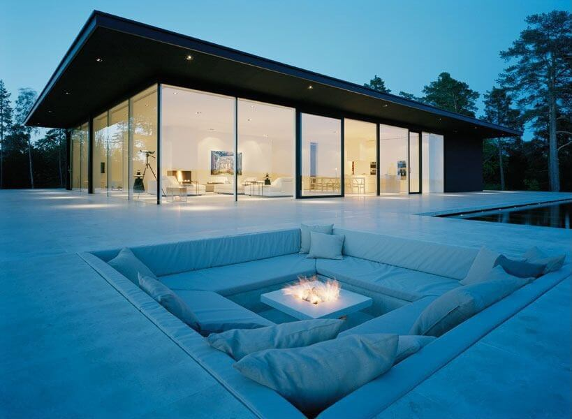 This sleek, minimalist upper level patio extends seamlessly from home interior through floor to ceiling glass, and includes cushionend conversation pit, with fire pit built into central white slab table.