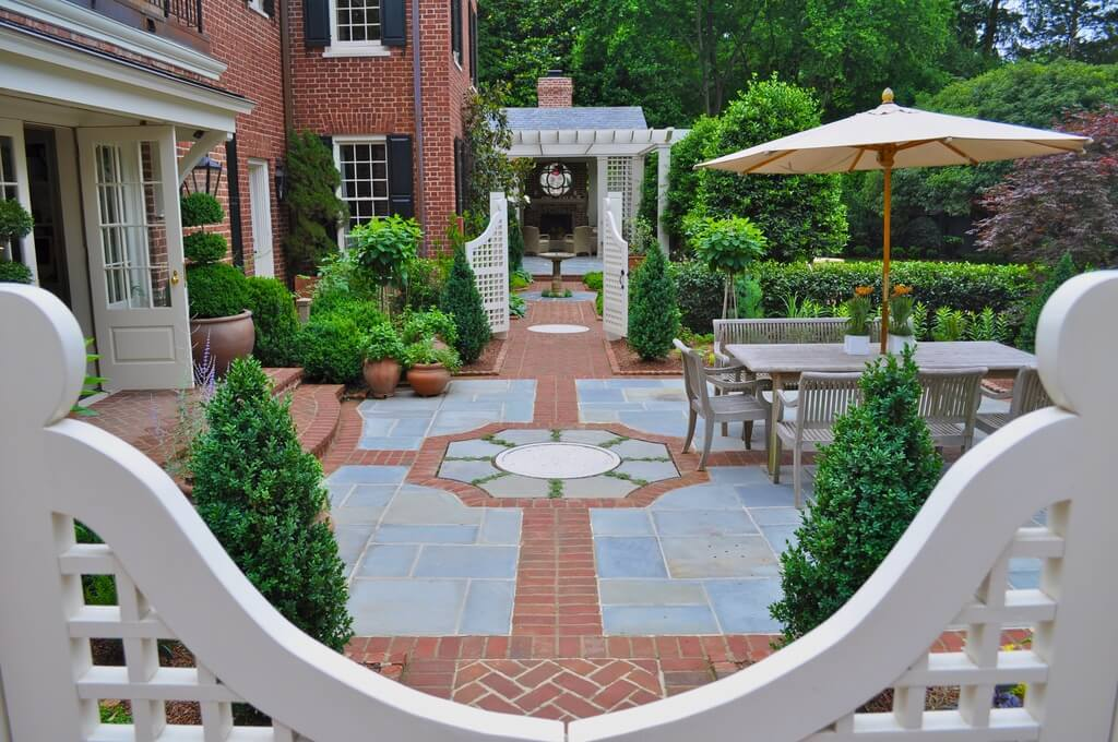 Red brick home features matching patio, accented with dark stone tiles. Shaped hedges and white gates enclose the space, featuring a plethora of plant life and natural wood dining table on right.