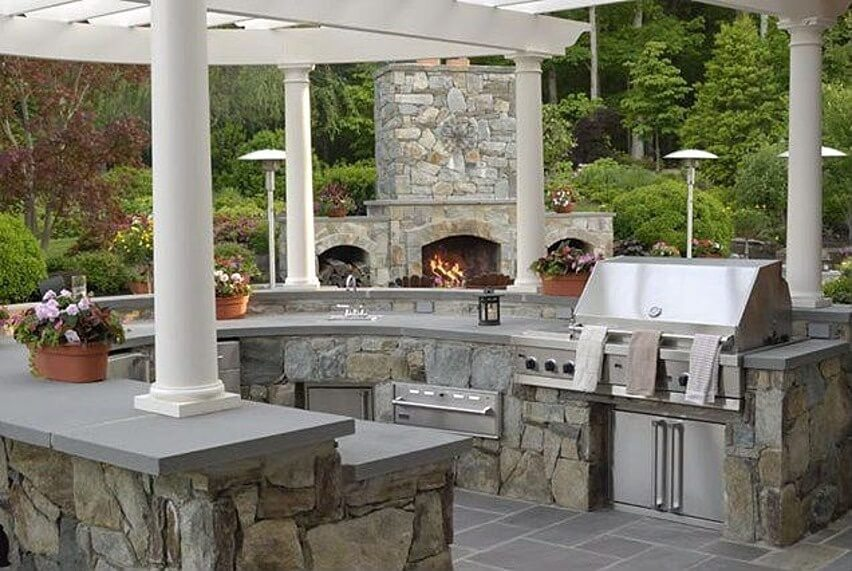 Elaborate stone structure and U-shaped island in this patio features oven, grill, and other appliances built in, beneath grey countertops. Matching stone outdoor fireplace stands at center.