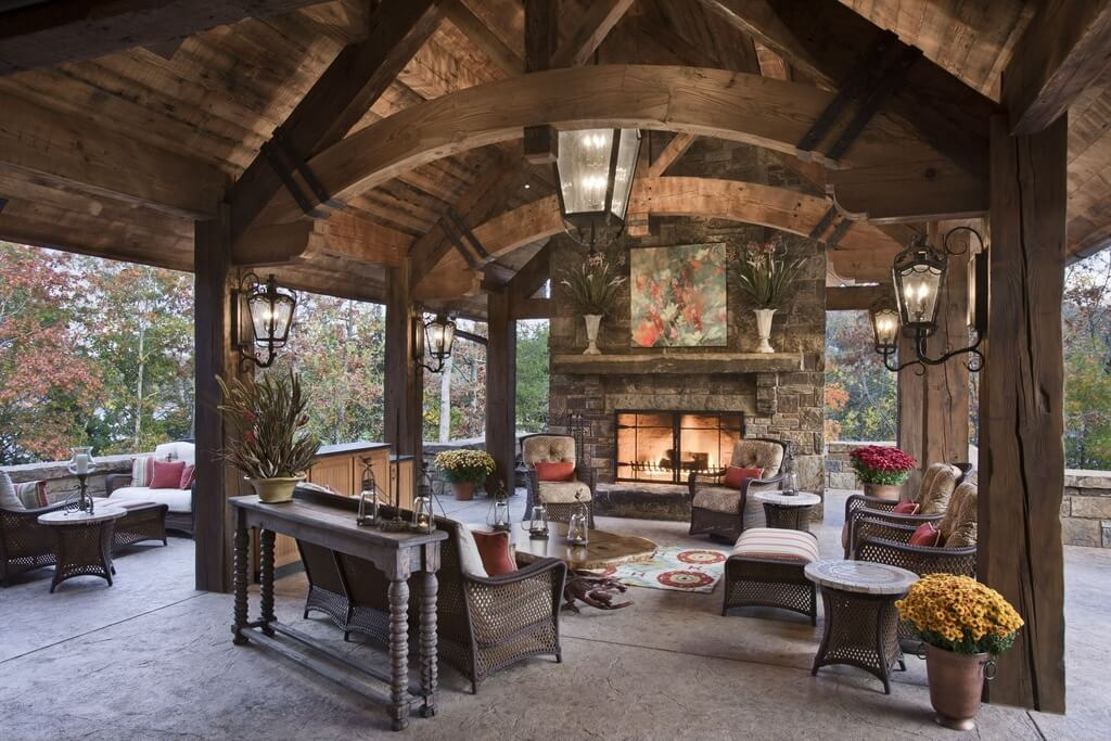 Here's another covered patio, featuring exposed wood beams and vaulted ceilng over stone flooring, with immense stone fireplace standing before carved wood table and surrounding wicker furniture set.