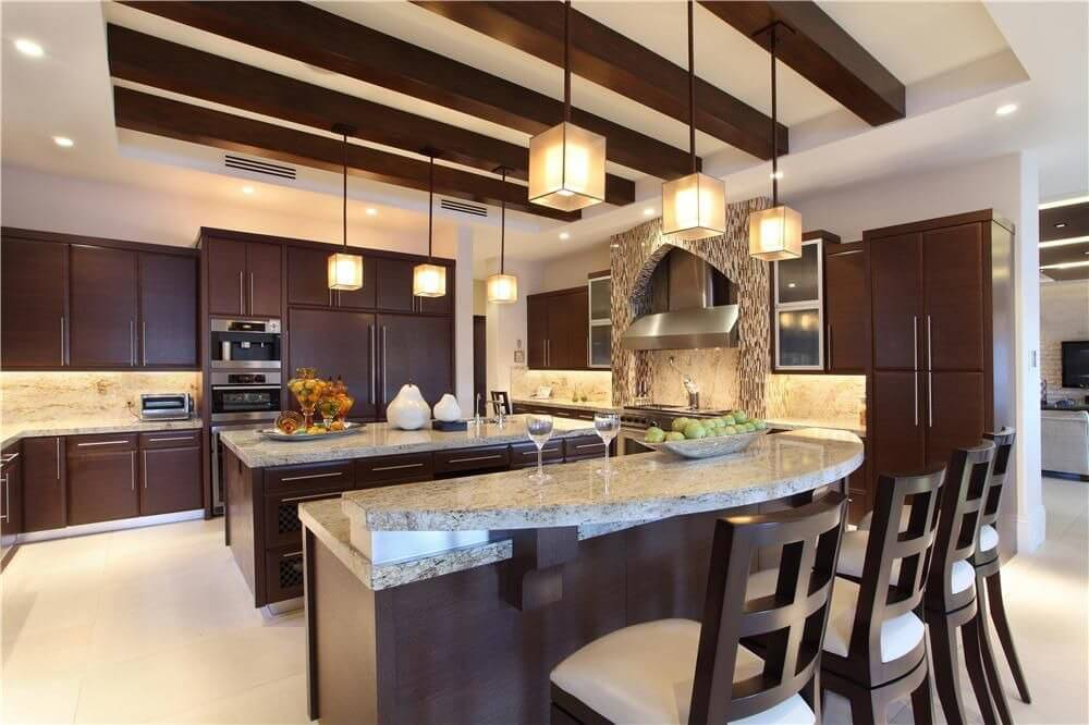 contemporary cabinetry with stainless fixtures against dark wood make up the design of this luxury kitchen