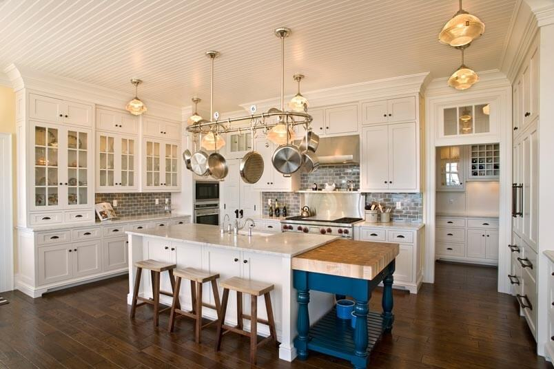 Luxurious White Kitchen With Wood Floor With A Splash Of Color Provided By A Bright Blue