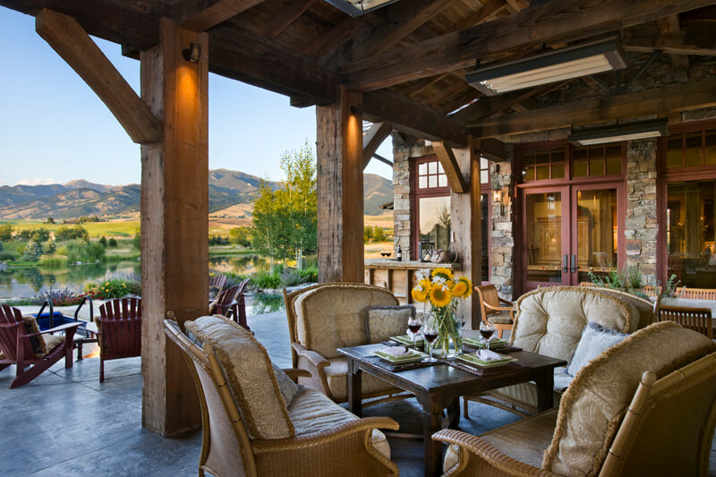 This rustic styled patio and home features large natural wood exposed beams in the open ceiling, as well as support pillars, over plush wicker furniture set around dark wood dining table.