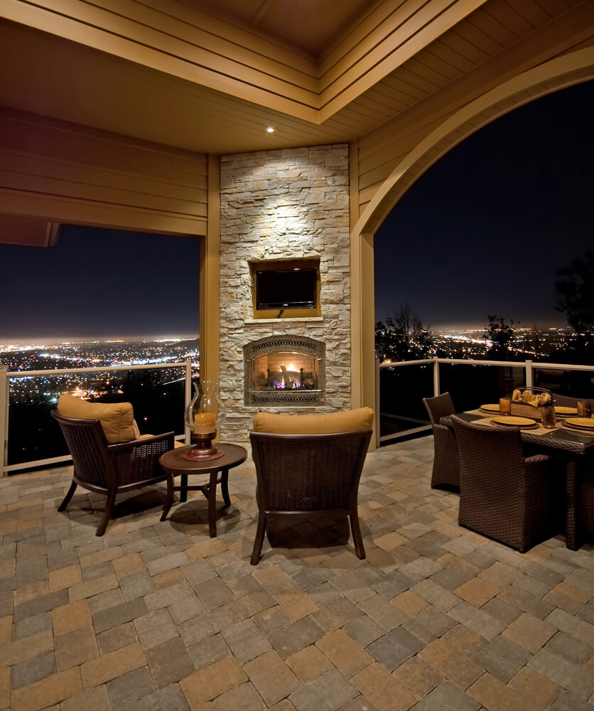 Upper level stone brick patio features corner fireplace wall with mounted TV above, dark wicker and burnt orange furniture set, and expansive views of valley below over metal and glass railings.