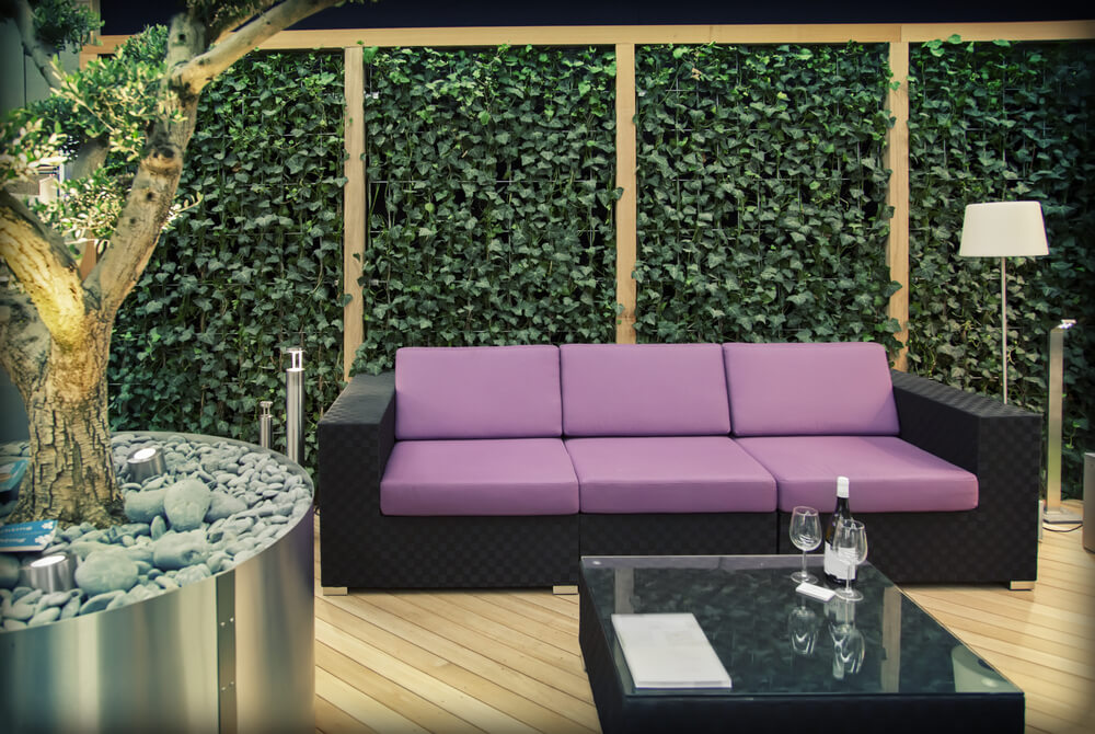 Light natural wood flooring supports black sofa with purple cushions in this patio, surrounded by ivy-laced privacy wall.
