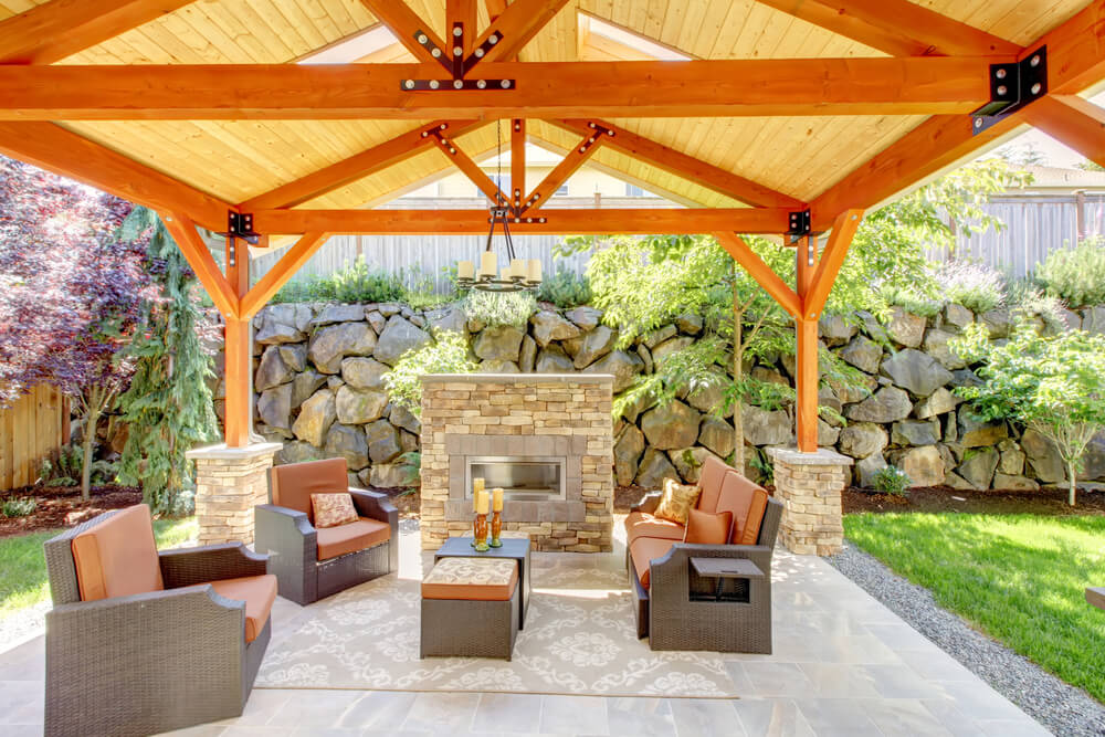 Bright tones throughout this patio include natural wood roof structure set on light stone brick columns, with matching gas fireplace standing before brown and orange wicker furniture set. The whole space is framed by large stone fence with greenery throughout.