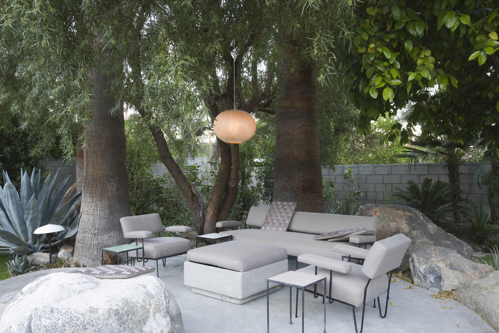 Minimalist, light toned patio with matching furniture set sits beneath massive trees, with globe-style chandelier hanging overhead. Large stones border the circular space.