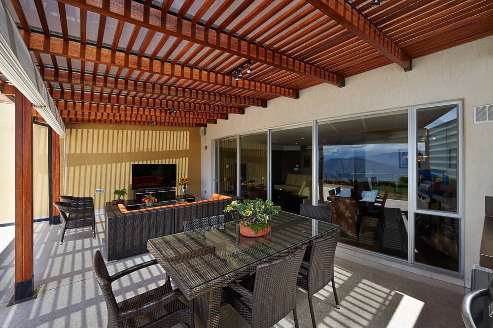 This cozy, enclosed patio is shaded by slatted wood roof, with dark wicker dining and living room style furniture sets next to floor to ceiling glass wall.