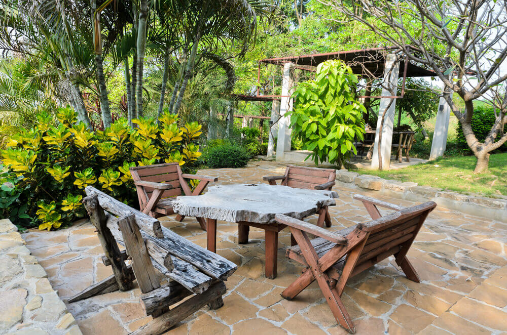 Ultra-rustic look patio features tree trunk slice table surrounded by natural wood seating over flagstone flooring. Enclosed dining space in background.