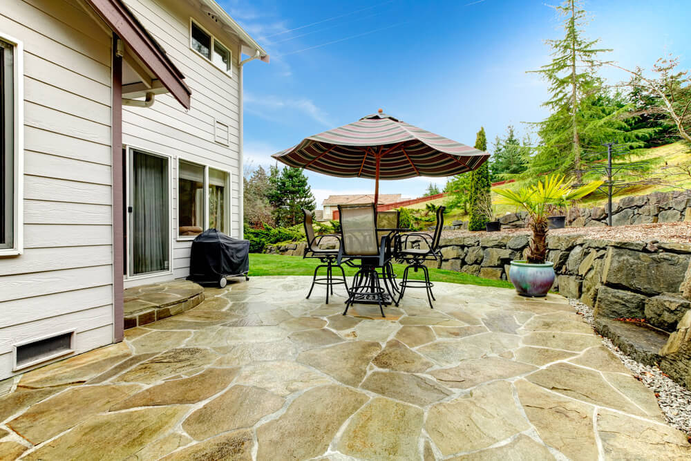 The natural stone flooring on this patio pairs with large stone walls laid into the sloping lawn at this home, with high level metal dining table and matching chairs at center.