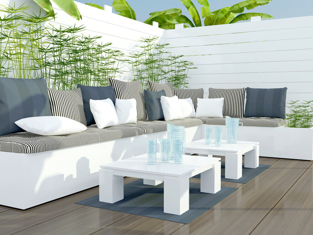 Contrast between bright white L-shaped seating and glossy wood deck defines this patio. Matching white privacy fence and twin coffee tables, plus greenery and patterned pillows accent the look.