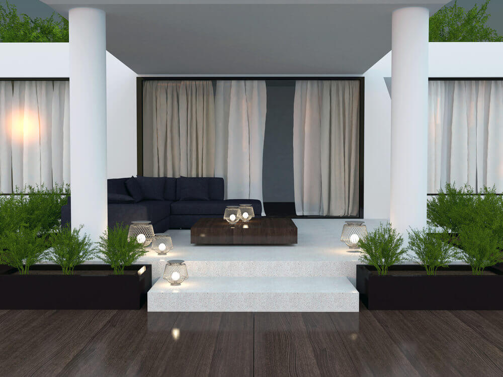 Sleek, minimalist style defines this patio. Stone upper level sits dark L-shaped sectional sofa and dark wood table between twin pillars, while lower wood level holds black rectangular planters, surrounding the white stone.