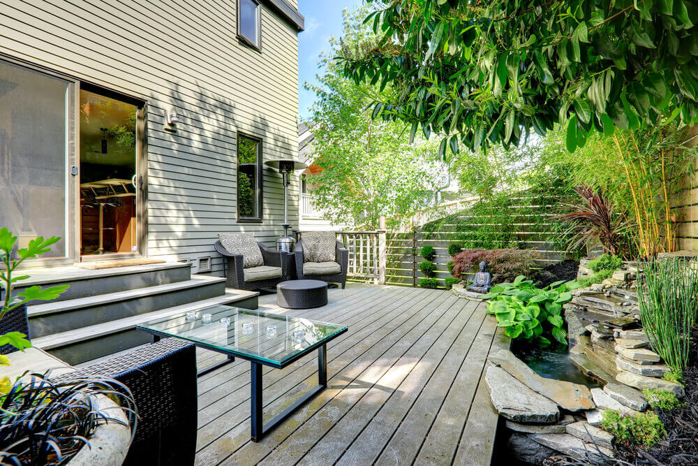 This natural wood patio sits next to an elaborate, compact Zen garden, featuring stacked flagstones, small pond, and Buddha statue beneath bamboo and wood privacy fence.