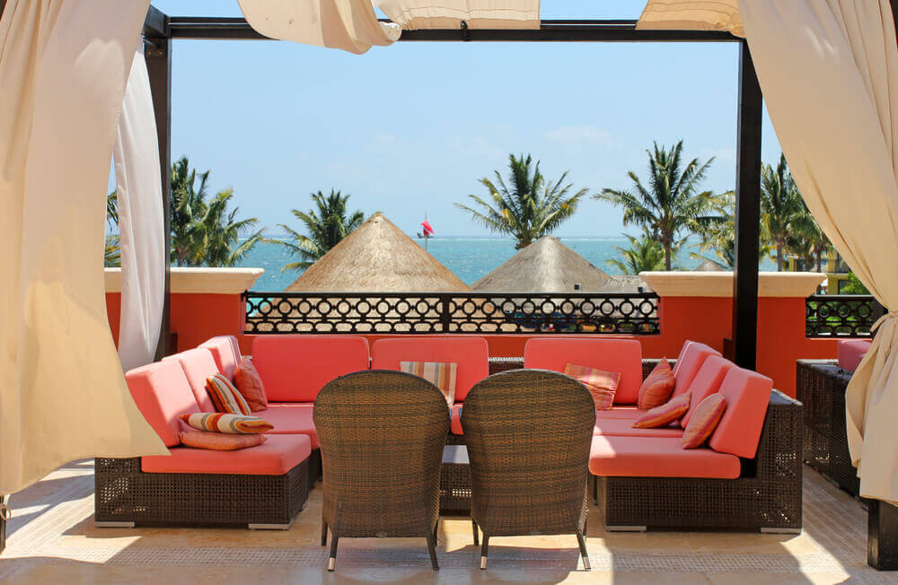 This seaside patio features bright contrast of red hued cushions on the dark wicker furniture, matching the low stone wall enclosure beneath black frames and billowing curtains.