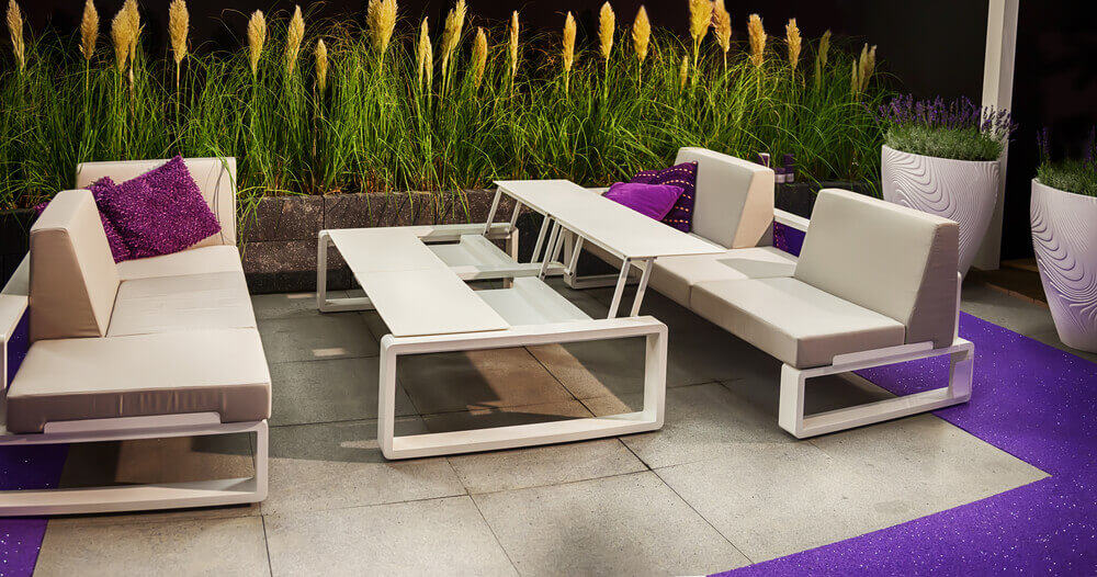 Unique, bright splashes of purple throughout this stone patio, including turf wraparound and accent pillows on the beige, thoroughly modern sofas. Transformable table sits at center.
