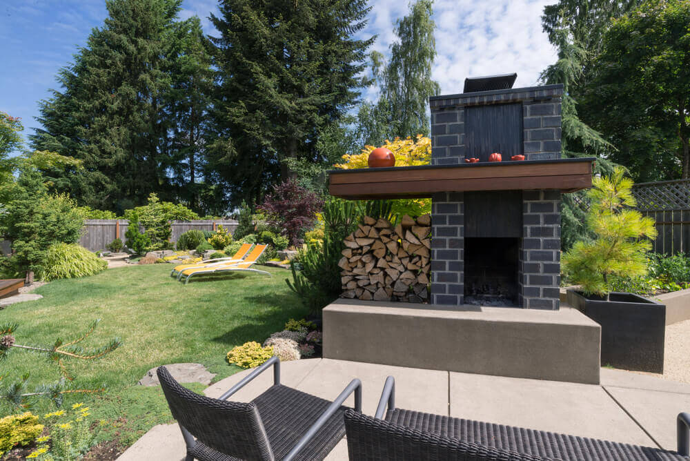 This concrete patio wraps around commanding brick fireplace with large wood mangle at center of this backyard.