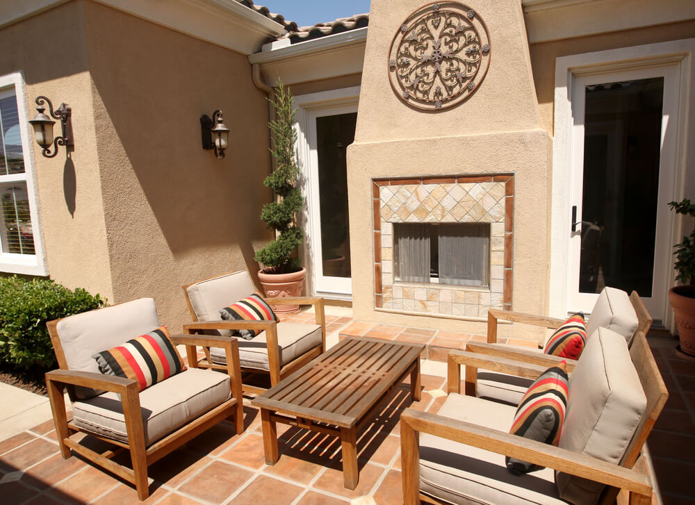This compact patio stands natural wood furniture and large tile fireplace over red tile flooring.