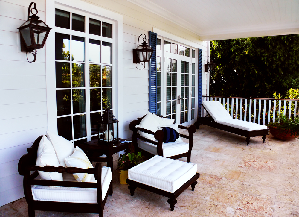 Cozy granite floored patio features high contrast black and white wooden furniture set next to French doors.
