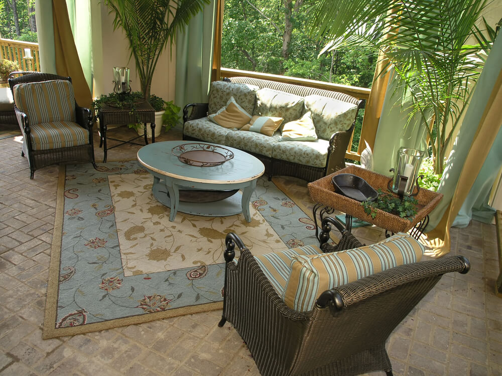 This tropical themed patio sets wicker framed, striped cushion furniture set around blue oval wood coffee table, with matching patterned area rug over brick flooring. Wood railings and blue and gold drapes surround the space.