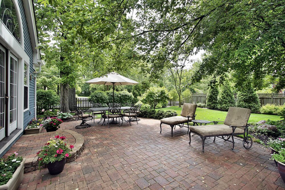 Large, simple design red brick patio holds full dining set with large table umbrella, plus twin lounge chairs next to lush garden.
