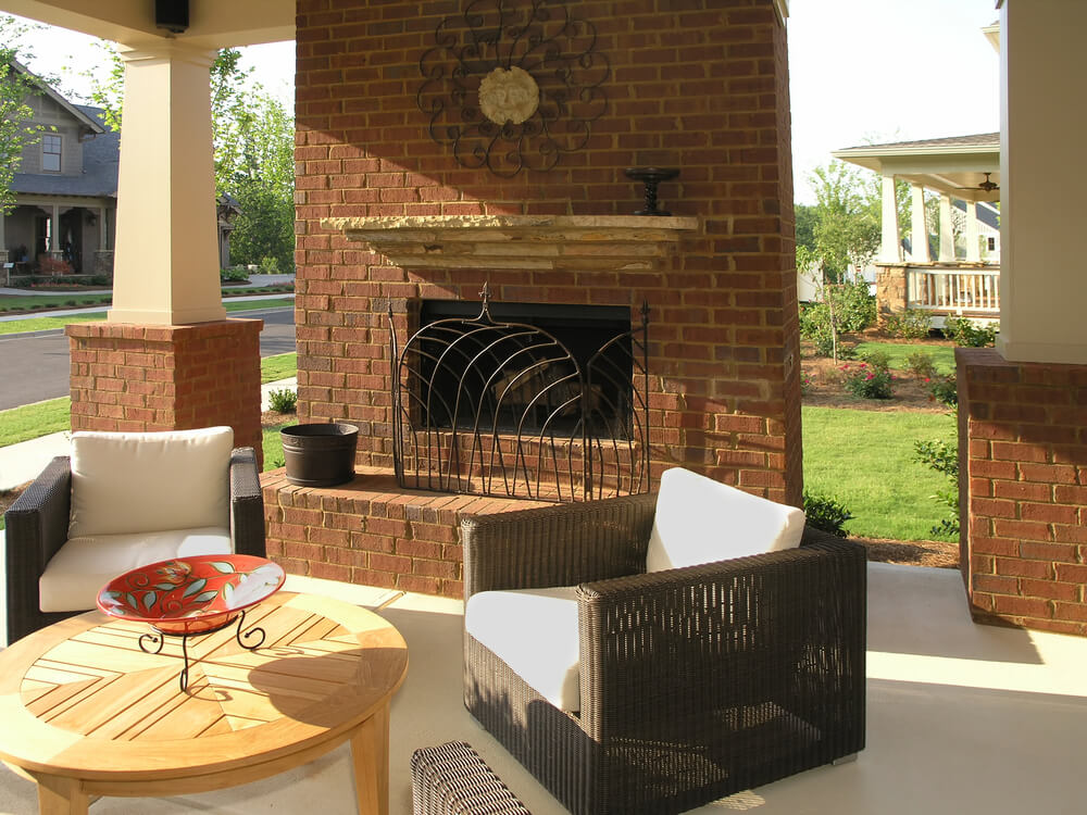 Here's a second view, highlighting round natural wood coffee table and brick fireplace detail.