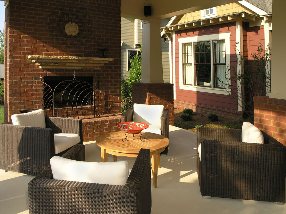 Here's another covered patio, featuring the contrast of dark armchairs with white cushions over off-white flooring, with red brick fireplace at left.