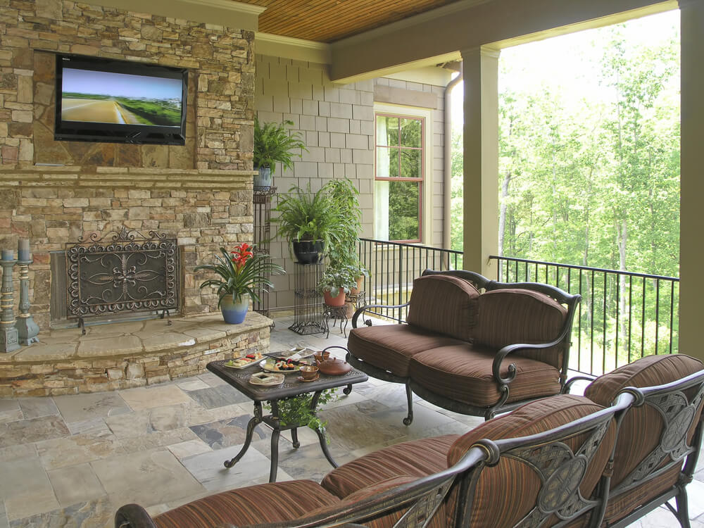 Covered patio features stone flooring, metal framed, brown cushioned furniture, and large brick fireplace with mounted television beneath natural wood ceiling.